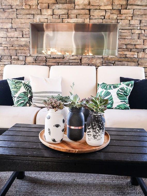 moderne tisch- und zimmerdekoration mit DIY blumenvasen aus weckglas in holztablett rund, akzentwand aus naturstein mit einbaukamin hinter sofa weiß