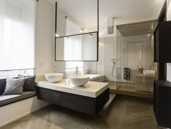 gestaltungsideen für modernes badezimmer mit sauna, badewanne und sitzbank entlag fensterbank und schwebendem waschtischschrank in schwarz mit runden waschbecken weiß