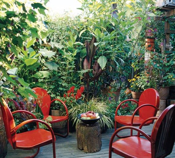 coole gartenideen für kleine gartenterrasse mit holzdiele, roten metallstühlen, baumstamm-tisch und viele kübelpflanzen