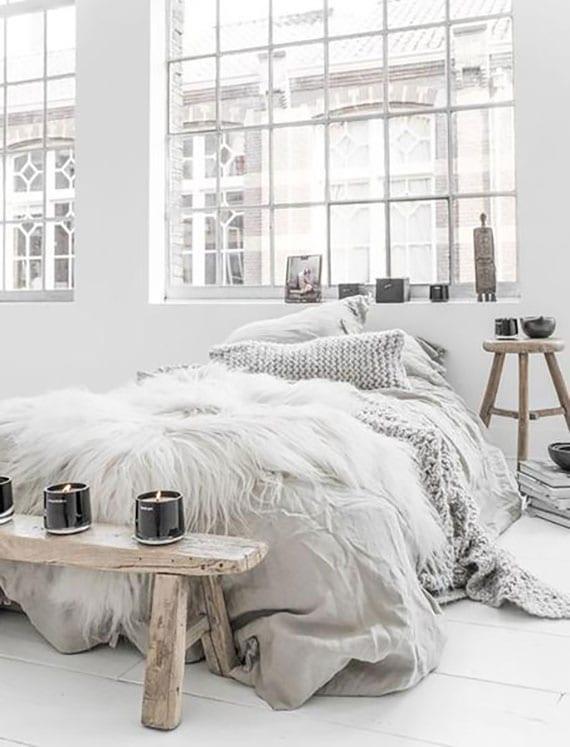 gemütliches schlafzimmer in weiß mit natürlichen füßboden aus holz, rustikalen beistelltischen holz mit schwarzen glaskerzen, bettwäsche und strickdecke in grau,fellteppich weiß