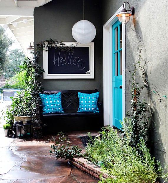 eingangsbereich attraktiv und individuell gestalten mit holzgartenbank schwarz,schwarztafel wanddeko, papierlaterne weiß, haustür in blau, laternen und mini-garten