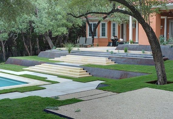 modernes und schlichtes garten design mit pool und terrassierung durch treppen und böschungen aus metall