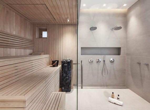 bad interieur design in grau und holz mit sauna, zwei duschköpfen für wand, praktischer wandnische und indirekter deckenbeleuchtung