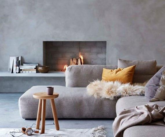 schlichte und moderne raumgestaltung in grau mit polsterecksofa, einbaukamin mit schweberegal, betonboden und holzbeistelltisch