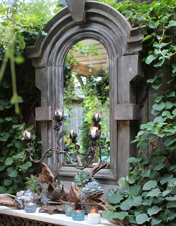 coole gartendeko idee mit rundbogenspiegel an holzgartenwand mit kletterpflanzen und beistelltisch mit diy treibholz-teelichthalter, kerzen und sukkulenten