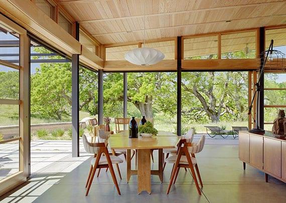 offenes wohnzimmer mit stilvoller Innengestaltung durch holzdeckenverkleidung, bodentiefe schiebefenstern, großformatigen bodenfliesen und holzmöblierung