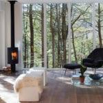 attraktives wohnzimmer interieur design mit bodentiefen fenstern, holzbodenbelag, skandinavischem kamin, rechteckigen beistelltisch-hockern weiß