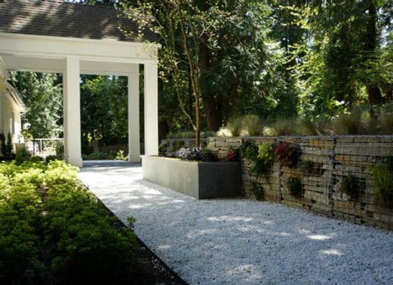 moderner hanggarten mit stützmauer aus gabionen und steinpflanzen
