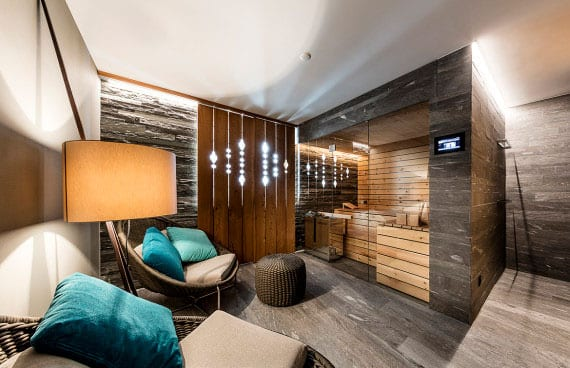 stilvolles interieur design vom privaten wellnesbereich mit kleiner sauna hinter verglasung, dekorativer sichtschutzwand holz, gemütliche sitzecke mit designer sesseln rund, wandverkleidung mit naturstein