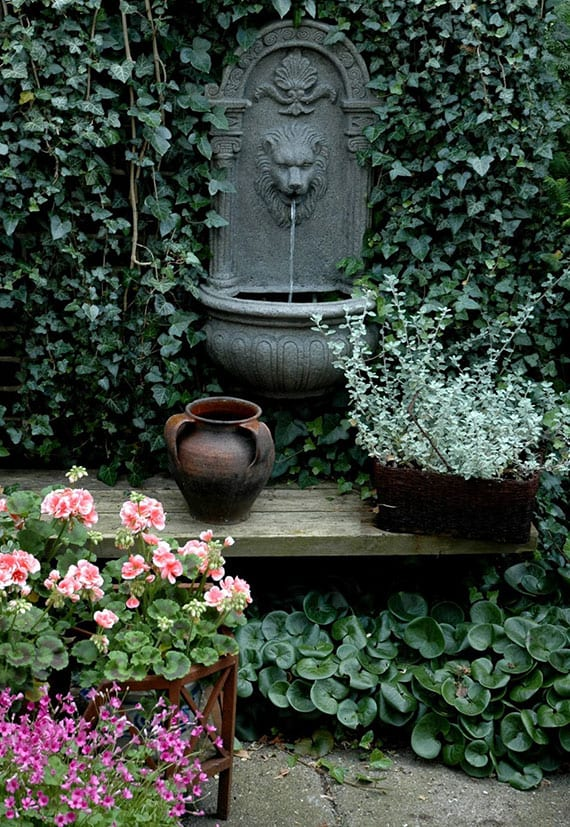 traumhafte gartengestaltung mit wasser durch springbrunnen mit löwenkopf and wand mit efeu, holzgartenbank mit weidenkorb und rosafarbigen blumen