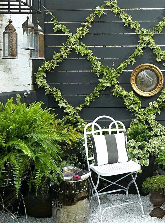 schicke gartengestaltung mit kiesboden, schwarzer schichtschutzwand holz, wandbegrünung mit efeu, hängenden laternen und grünen pflanzen, klappstuhl weiß, rundem beistelltisch silber und verschiedenen blumenkübel in schwarz