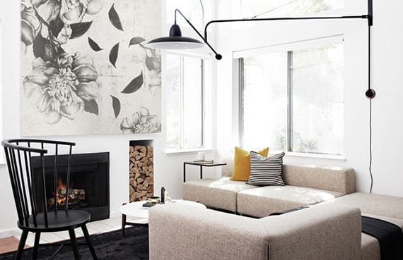 kleines wohnzimmer elegant einrichten im nordischen wohnstil mit ecksofa in beige, schwarzem teppich, einbaukamin mit nische für feuerholz, wanddeko mit blumen-leinwandbild und designer-wandlampe