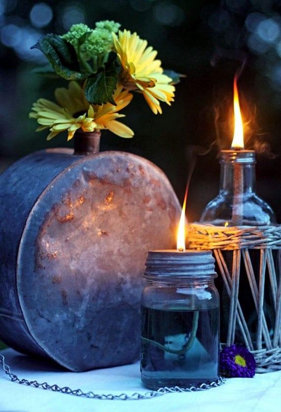 kreative terrassendeko mit selbstgemachten Öllampen aus einmachglas und glasflasche und vintage blumenvase aus metall
