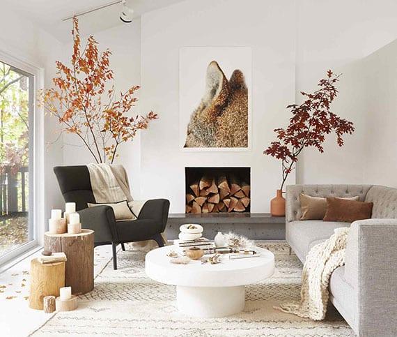attraktive raumgestaltung wohnzimmer in weiß und grau mit modernem sofa, rundem couchtisch weiß, baumstam-beistelltischen, kamin mit feuerholz und herbstdekoration mit zweigen in vasen
