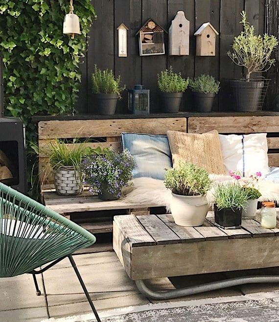 coole terrassengestaltung mit schwarzer sichtschutzwand holz, diy gartensofa und kaffeetisch aus paletten, teppich, kräuterpflanzen in schwarzen terrakotta blumentöpfenn und vogelhäuser als frische dekoration
