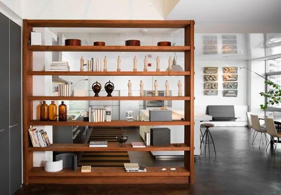 moderne wohnung mit offenem grundriß stilvoll gestalten mit grauem betonboden, küche mit kochinsel weiß, raumteiler-regal aus holz