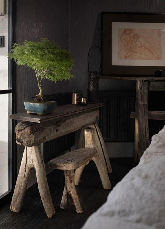 natürliche zimmergestaltung im asiatischen stil mit wandfarbe grau, dunklem holzboden, rustikalen beistelltischen aus verwittertem holz und bonsai-baum