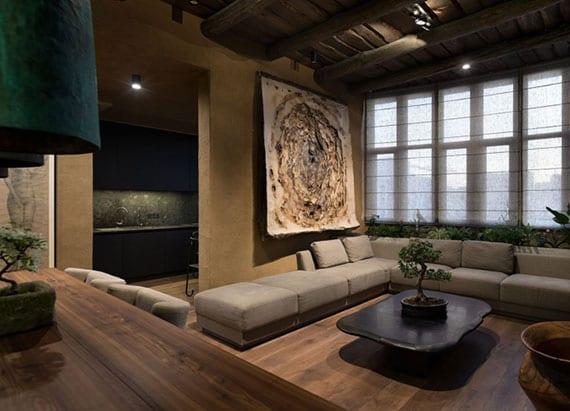 kleine wohnung mit modernem zen-interior im wohnesszimmer mit holzboden, sandwandfarbe, polstersofa beige, rustikalem holzcouchtisch, modernem esszimmertisch aus holz, schwarzer küche und handgefertigter wanddeko