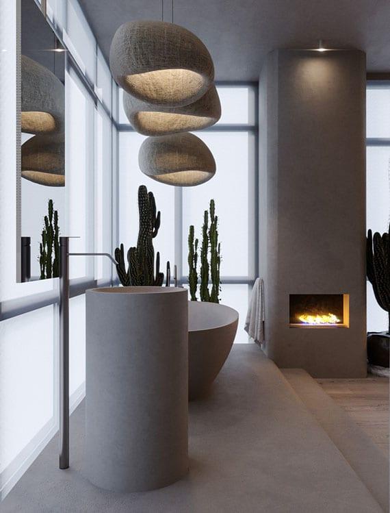 luxus-badgestaltung mit kamin, freistenden badewane und waschbecken rund, designer stooff-pendellampen, hängespiegel vor glasfassade und kakteen in pflanzenkübeln