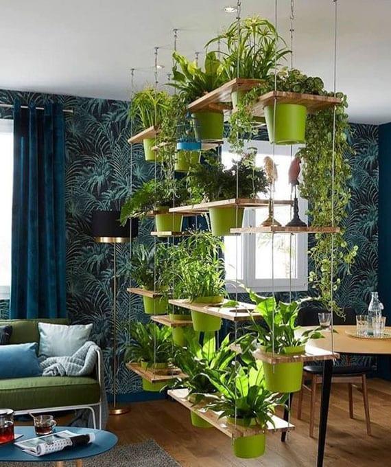 schickes interieur design in blau für kleine wohnungen mit wohnessbereich, wandtapete mit palmenmotiv, dunkelblaue vorhänge, sofa grün, rundem esstisch holz mit schwarzen lederstühlen und diy hängeregal für topfpflanzen als raumteiler