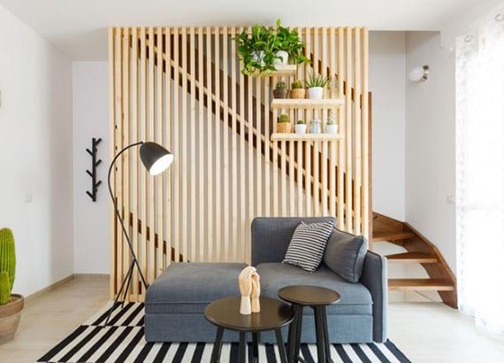 kleine Maisonette modern gestalten mit trennwand holz vor innentreppe, kleinem polstersofa grau, stehelampe schwarz, runden beistelltische schwarz auf teppich mit streifenmuster