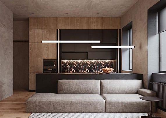 schlichte und elegante gestaltung kleiner wohnküchen mit kochinsel schwarz, grifflosen holzfronten der küchenschränken, niedriger polstersofa grau, holzbodenbelag und wandfarbe grau