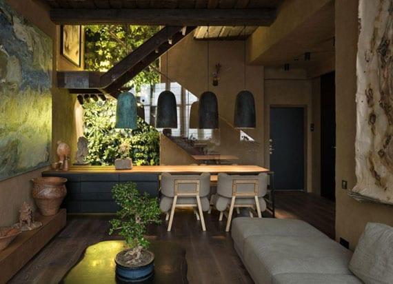 japanisches einrichtungskonzept für kleine wohnzimmer mit essplatz, offener innentreppe , vertikkaler begrünung,wandgeastaltung in braun, schwarze pendelleuchten über kücheninsel tisch holz mit polsterstühlen