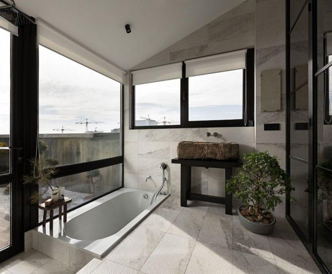 modernes einrichtungskonzept für badezimmer im asiatischen stil mit bodenebener badewanne, holzwaschtisch in schwarz mit stein waschbecken, weißen marmorfliesen, dusche mit schwarzen glastüren, schwarzen fensterrahmen mit weißen sonnenschutz-rollos und kleinen bonsai-bäumen