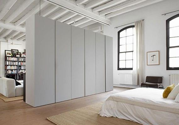 kreative raumteiler ideen für attraktive einrichtung einer loft wohnung mit weißem kleiderschrank als trennobjekt, holzbalkendecke weiß, holzfußboden und bogenfenstern mit schwarzen rahmen