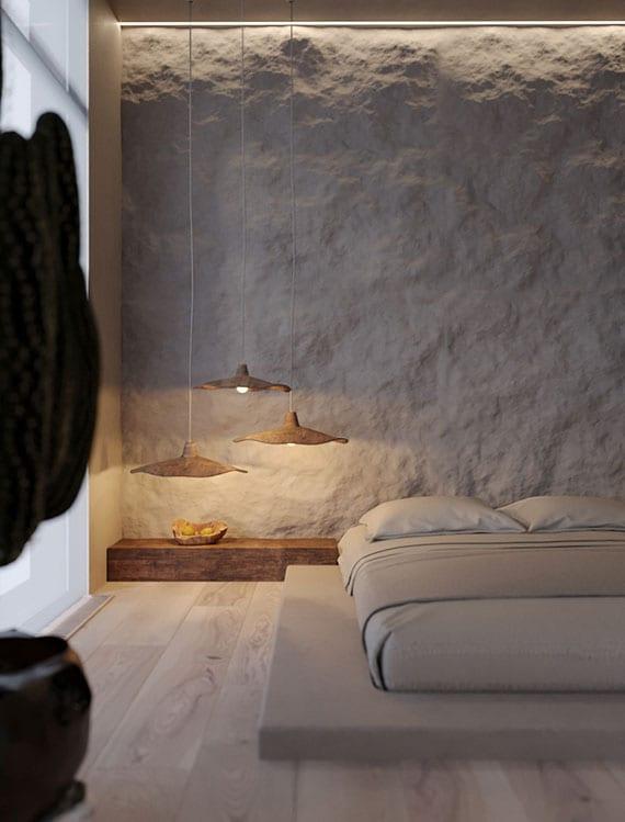 schlichte und originelle schlafzimmergestaltung im asiatischen stil mit matratze auf holzpodest, designer-pendellampen, akzentwand hinterm bett aus weißem naturstein, indirekter deckenbeleuchtung