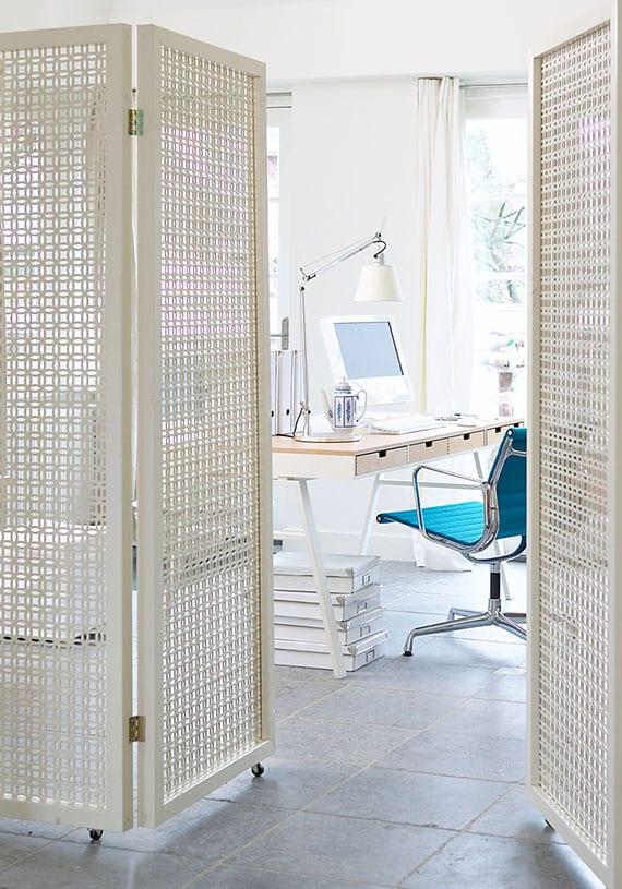 modernes homeoffice mit weißem schreibtisch holz mit schubladen praktisch trennen vom wohnzimmer durch flexiblen Paravent