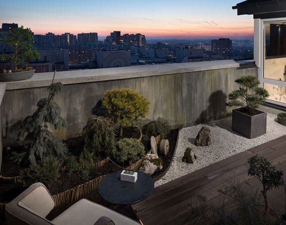 coole balkongestaltung mit kleinem steingarten, japanischen pflanzen in blumenkübeln, holzbodenbelag für kleine sitzecke mit polstersessel und rundem beistelltisch