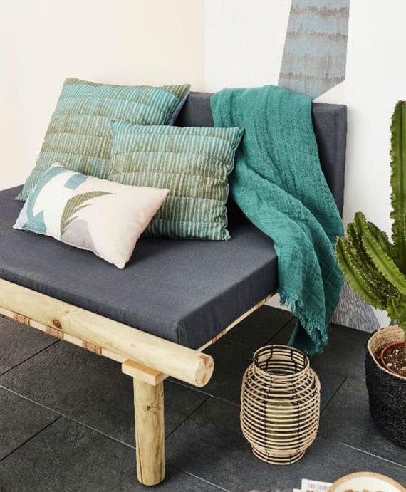 gartensofa aus holz selber bauen und mit grauen polsterkissen und bunten dekokissen und blauer sofadecke einrichten