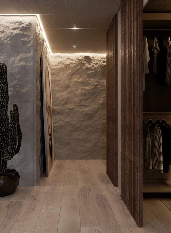 coole gestaltungsideen flur mit wandverkleidung aus rohem stein, indirekter deckenbeleuchtung, hellem holzboden und garderobe in wandnische mit holzschiebetür