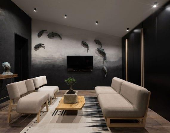 kleines wohnzimmer nach dem japanischen einrichtungskonzept attraktiv gestalten mit niedrigen sitzmöbeln aus holz und polsterung in beige, holzcouchtisch mit bonsaibaum,schwarzem kleiderschrank, akzentwand mit fischen hinter tv-gerät