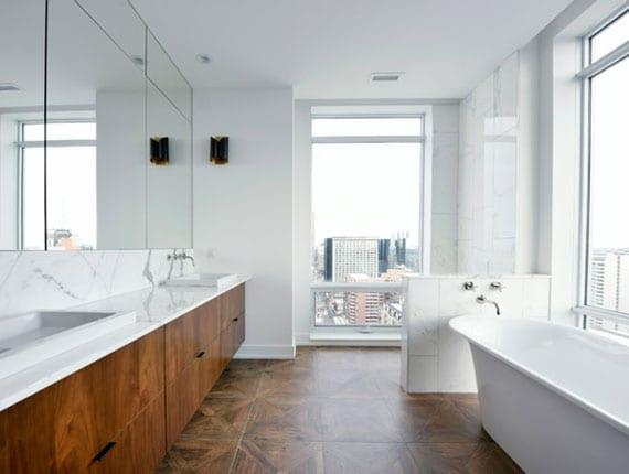 großzügiges badezimmer mit parkett, waschtischschränken aus holz und freistehende badewanne mit blick durch ein panoramafenster