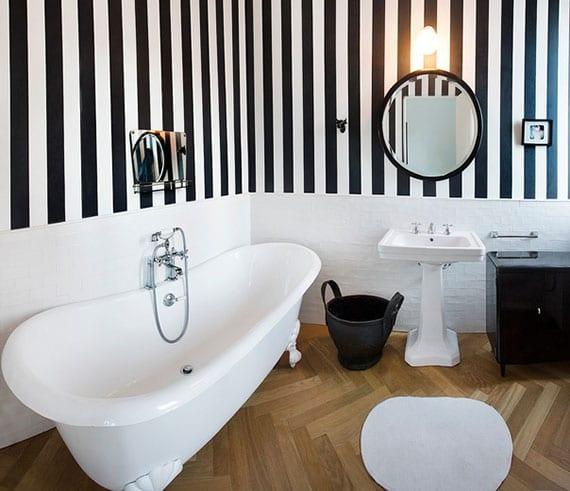 kleines bad stilvoll gestalten mit streifen-tapete in schwazweiß, ziegelwand weiß,badewanne mit löwenfüßen, schwarzen badaccessoires und fischgrätparkettboden