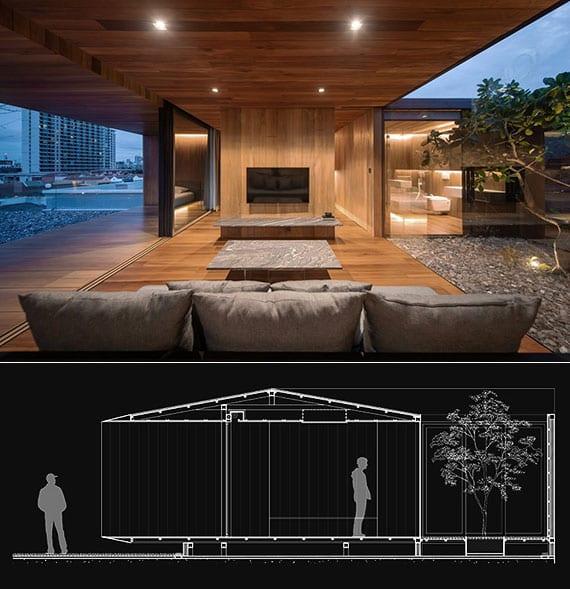 modernes wohnzimmer in holz mit polstersofa grau, modernem couchtisch mit natursteinplatte, schiebefenstertüren zur holzveranda und panoramablick zum hofgarten mit kiesboden und led beleuchtung