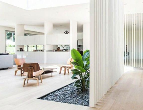 natürliche raumteiler idee für wohn- und arbeitsbereiche mit Holztrennwand und steingarten mit grünen pflanzen