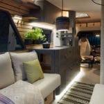 modernes reisemobil mit schlafdach, sonnenterrasse mit grill, luxus bad mit naturstein, kompakte küche und treppe mit schubladen