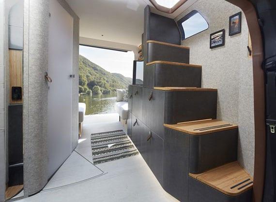 modernes reisemobil mit kompaktem raumbad, sitzgruppe mit küchenzeile und fester holztreppe zum schlafbereich