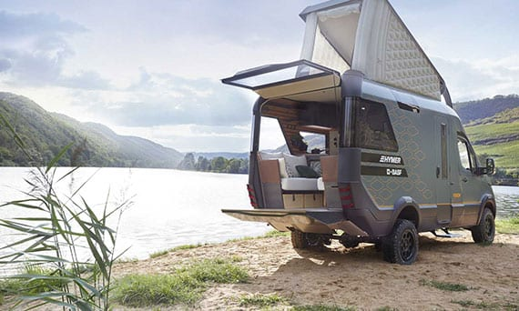 ein reisemobil mit separatem schlafbereich auf dem dach und bequemer sitzgruppe mit terrasse