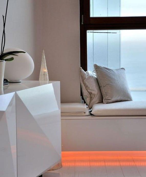 modernes interieur design in weiß mit kuscheliger sitzbank vor dem fenster mit einbau led leuchte in orange