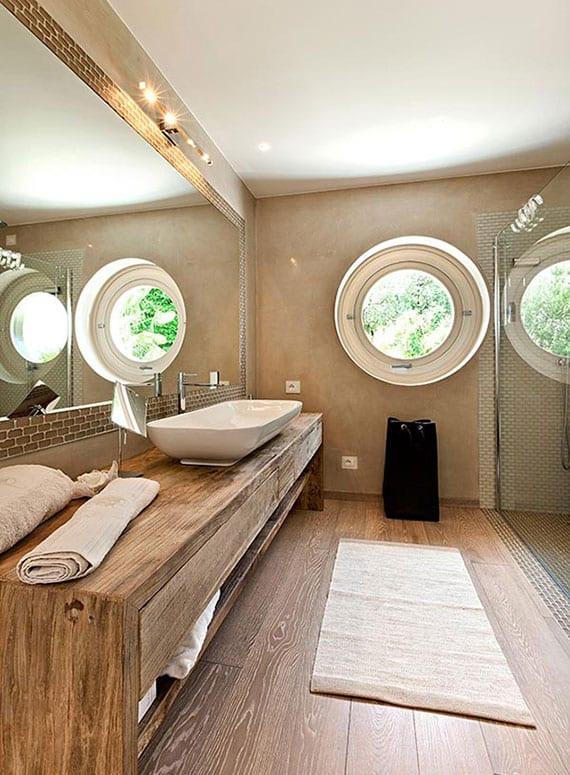 schicke badgestaltung in beige mit rundfenster, holzfußboden, holzwaschtisch, großerm badspiegel gegenüber dusche mit glastrennwand