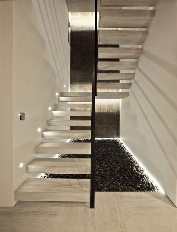 offene natursteintreppe in hellgrau mit kragstufen attraktiv gestalten mit indirekter wandbeleuchtung,akzentwand schwarz und kiesboden aus loser kieselsteinen schwarz