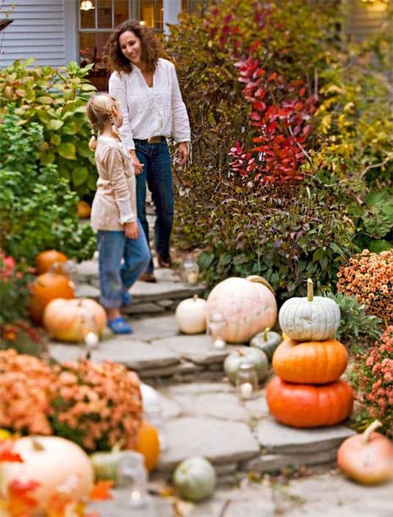 coole herbstdeko ideen zu halloween und für partys mit kürbis-thema_gartenweg und außentreppe mit kerzen, herbstblumen und verschiedenfarbigen kürbissen dekorieren