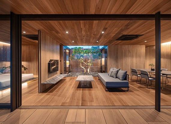 wohnbereich mit zen interieur design in holz und baum in glasatrium