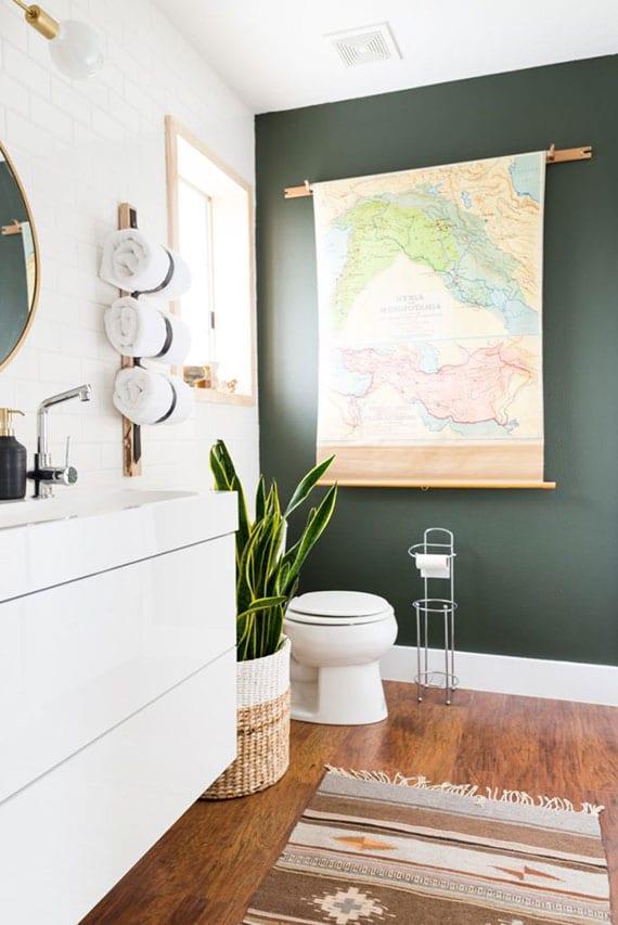 natürliche badgestaltung mit holzboden, akzentwand in grün, wandfliesen und waschtisch in weiß, deko mit weltkarte an der wand und zimmerpflanze im weidenkorb