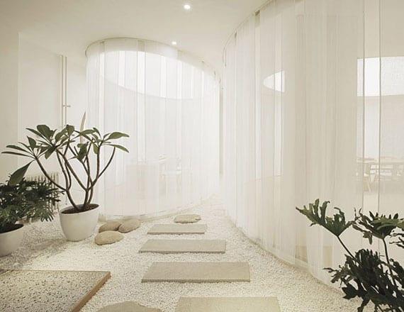 coole gestaltungsidee für weißes interieur mit kiesboden, trittsteinen, grünen topfpflanzen_attraktive raumteilung mit weißen gardinen
