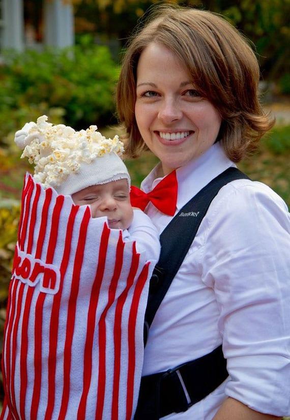 coole idee für lustiges baby faschingskostüm als popcorntüte aus babytragtasche mit roten streifen und babymütze mit popcorn